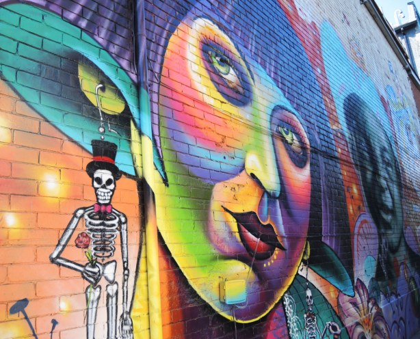 part of a large mural on the side of a 2 storey building, a large multicoloured woman's face. She is wearing earrings that look like skeletons
