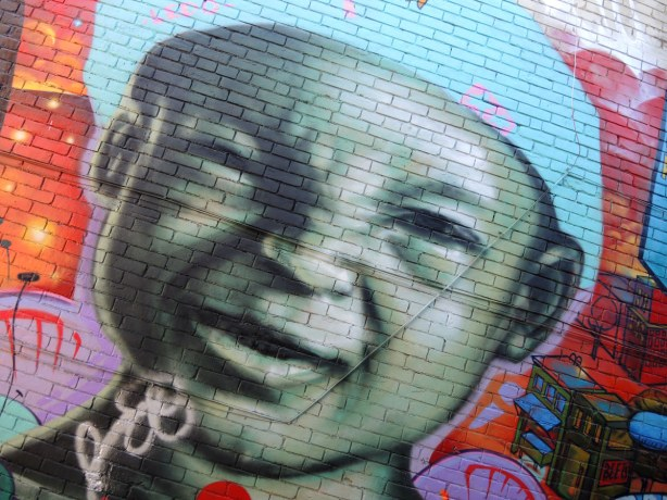 part of a large mural, a picture of a smiling small boy wearing a light blue cap. It is very large.