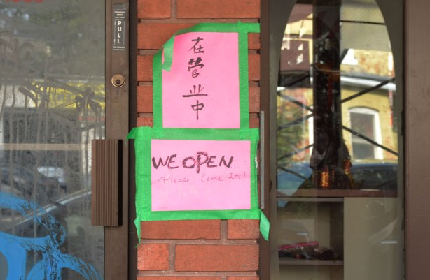 A pink sign that has been taped with green tape beside the entrance of a shop that says We open.  Please come in.