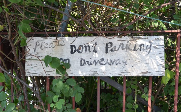 A sign on a fence beside a driveway that says Please don't parking on driveway.