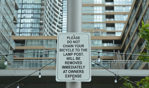 Sign by a sidewalk that says Please do not chain your bicycle to the lamp post.  Will be removed immediately at owner's expense.  Large condo towers are behind the sign.