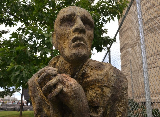 close up of one of the sculptures in Ireland Park.  It is a man with his hands clenched in front of him and a worried look on his face.