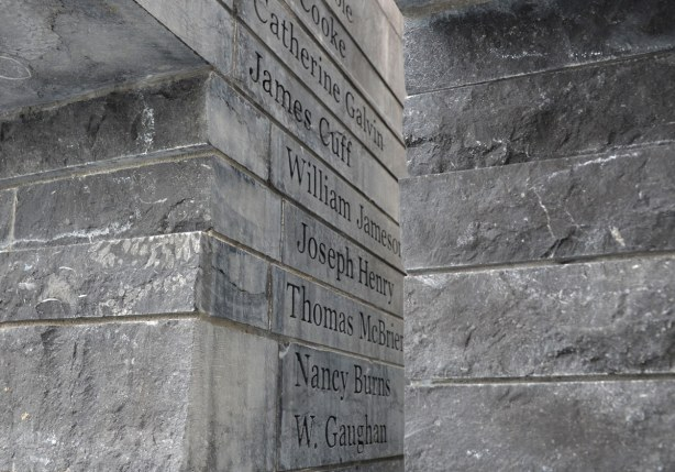 Names in black lettering carved into the side of limestone.