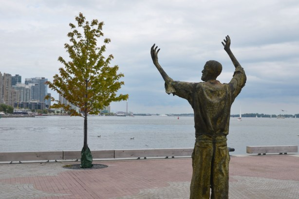 Sculpture of a man with his arms upraised.  He is looking over part of the harbour towards downtown Toronto.