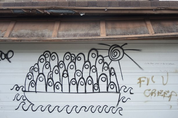 Graffiti in an alley, a large number of finger like creatures in a boat.  Black line drawing on white garage door.