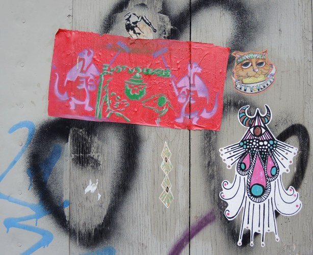 Graffiti in an alley,  a few stickers on a grey wood wall - the head of a cat, a small horse and an abstract drawing.