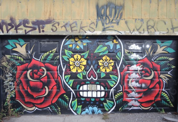 a garage door that has been painted with two very large red roses on either side of a painting of a skull with lots of flowery motifs in it.