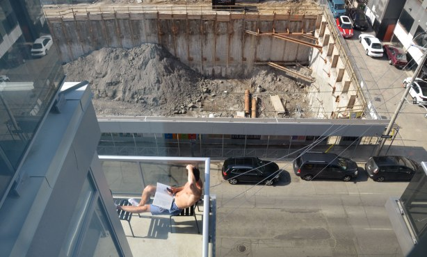 Looking down at a man who is sitting on his balcony and reading a book.  Across the street is an open hole where a new condo is being constructed