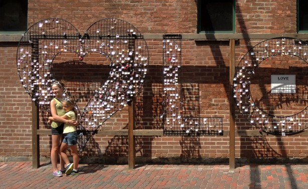 two sisters are hugging while having their picture taken in front of a large wire mesh heart.  The word LOVE is spelled in large wire mesh letters.  People have locked padlocks onto the wires.