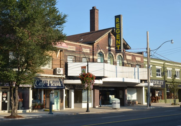 The front of the Regent theatre, a two storey red brick building with a large ugly blank white sign across the bottom of the upper storey.