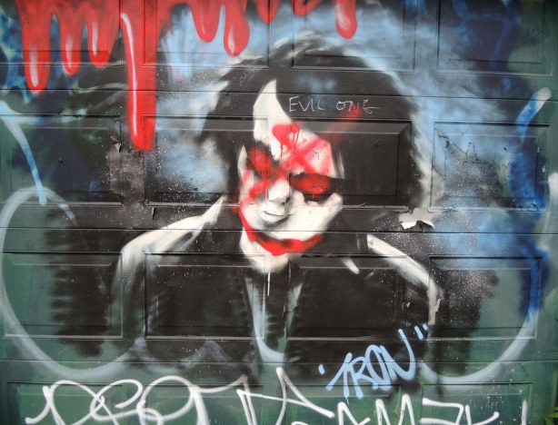 Graffiti man's head with red eyes and mouth.  Red paint that looks like blood dripping is above him.