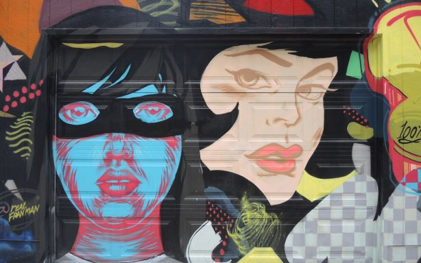 Street art piece of two large women's heads.  One is blue and she's wearing a black mask.