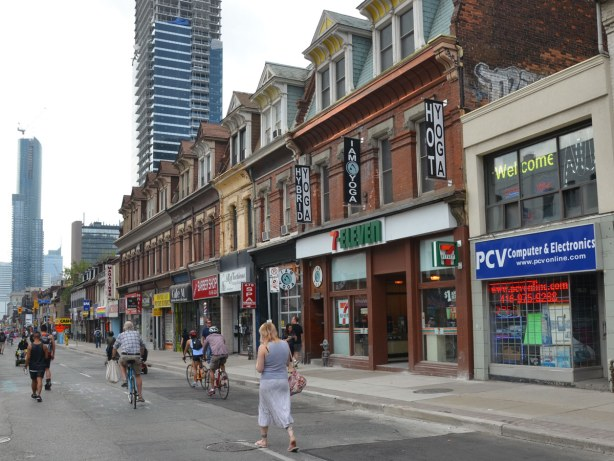 row of three storey buildings on Yonge St.  Brick buildings with storefronts on the ground floor.