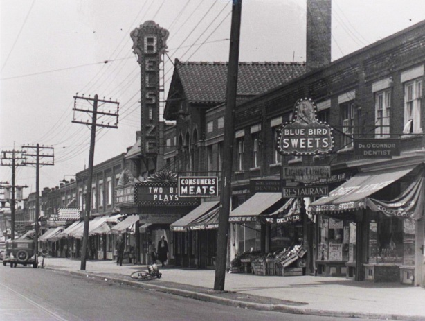 old black and white photo of a stretch of Mt. Pleasant showing some stores and the Belsize Theatre.