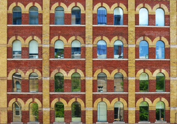 Four storey brick building with large windowes with rounded arched shaped tops.  Yellow brick details around the tops of the windows.