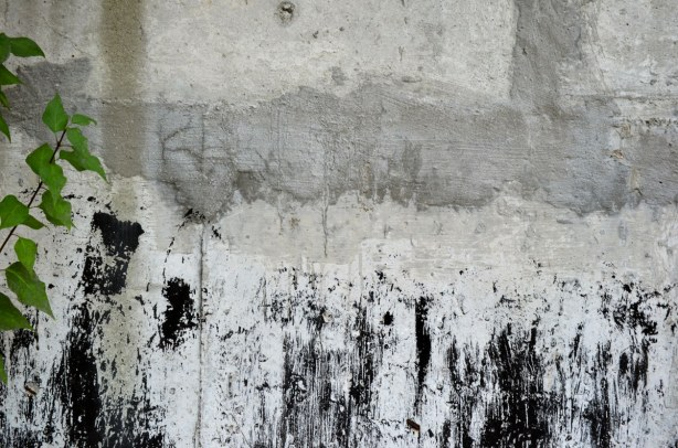 close up of a concrete wall that has black paint (or something like black paint) spilled on the lower part of it.