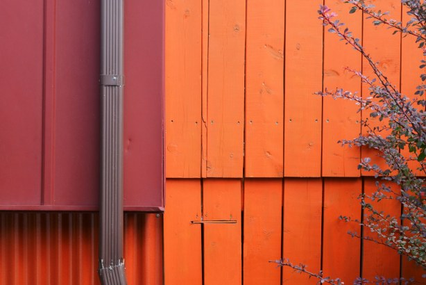 close up of a maroon coloured drain pipe down the side of a house that is red and orange.