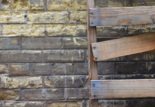 Close up showing part of a wood pallet that is leaning against a grey brick wall.