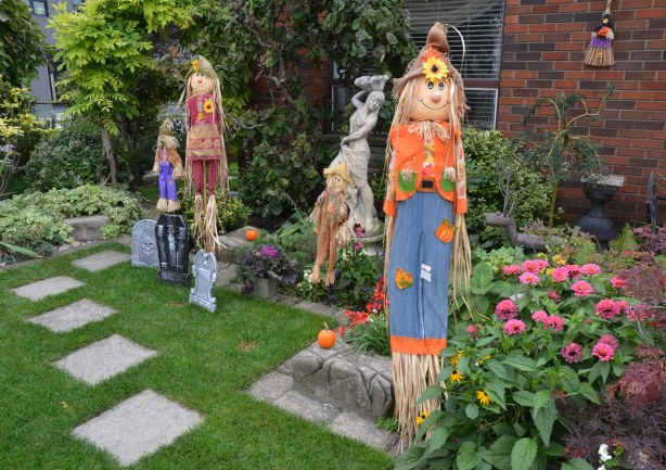 A front yard has autumn decorations - straw men in funny hats and patchwork clothes.