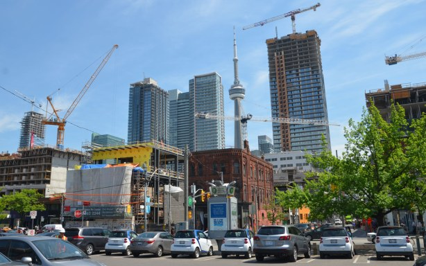 downtown cityscape with tall buildings as well as the CN Tower.  Lots of construction cranes in the picture.