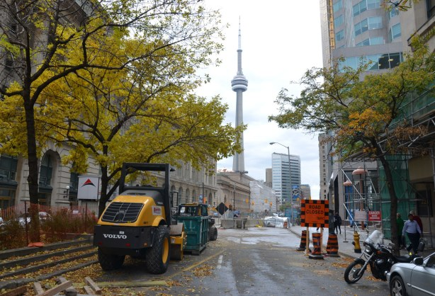 looking west on Front St. towards Union Station.  Construction equipment is in the foreground of the photo.  The CN tower is in the background.