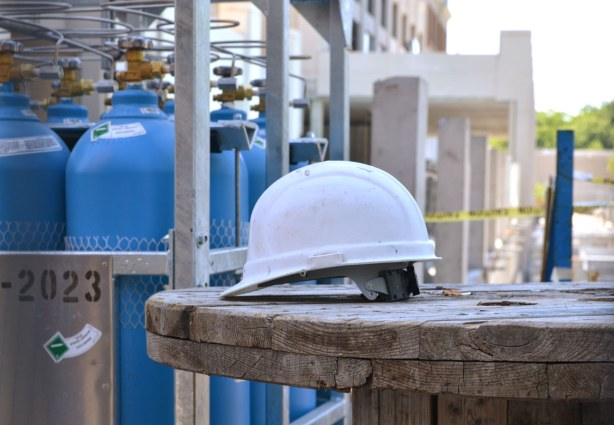 A white hard hat sits on the end of a large wooden spool.   Blue gas cylinders are behind it.