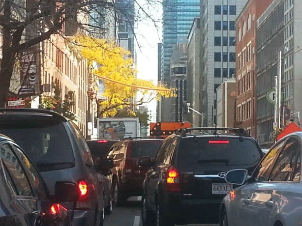Cars trying to merge from three lanes to one.  Large sign with arrow pointing left.  Tall buildings on either side of the street.  Yellow leaves on the trees because it is October.