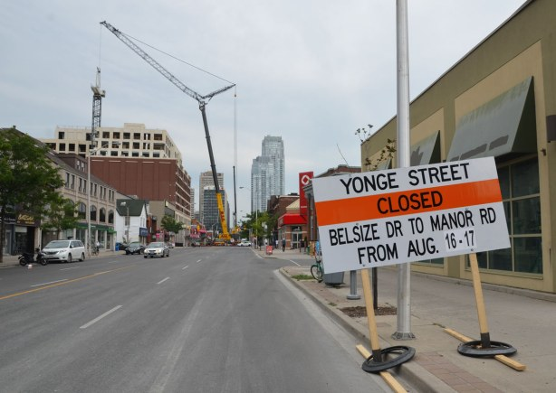 Yonge street is closed by a large crane that is parked in the middle of the street.