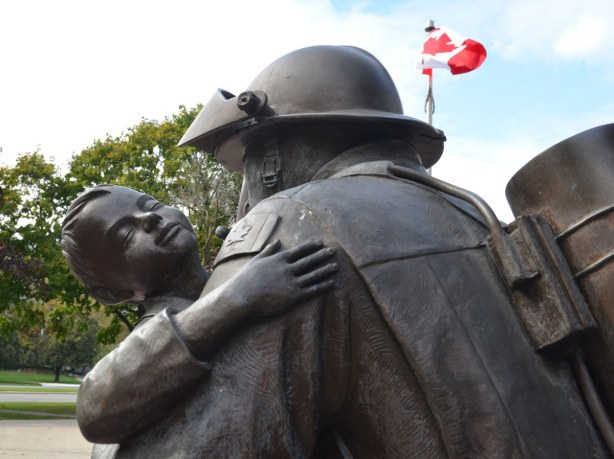 close up of statue of a firefighter carrying a young boy