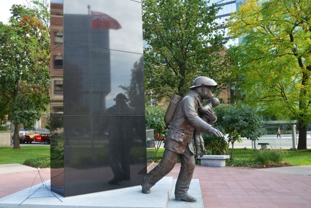 Statue of a firefighter wearing a gas mask and carrying a young boy is in front of a block of shiny black rock.  In the rock there is a reflection of the statue along with the Ontario flag that is flying nearby.