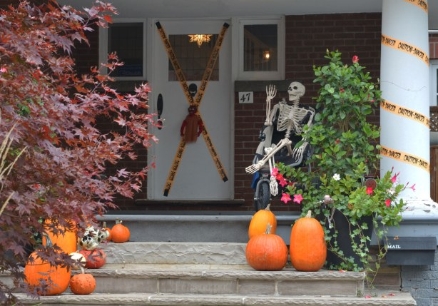 A skeleton is sitting on a front porch along with a number of pumpkins