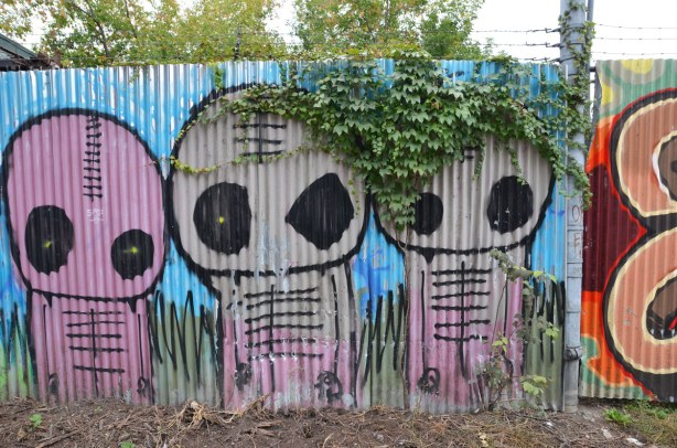 Three large pinkish alien like creatures on a corrugated metal fence.  Some ivy is hanging over the fence