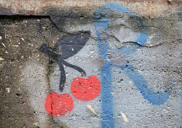 close up of a stencil graffiti of 2 cherries.  Beside the cherries is the letter R in blue.  Both are on concrete with a crack in it