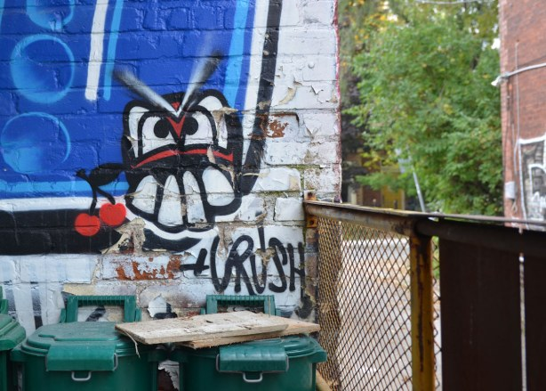 A silly face with big teeth with the word crush under it, graffiti on a wall in the alley.  Green garbage bins in front of the wall.
