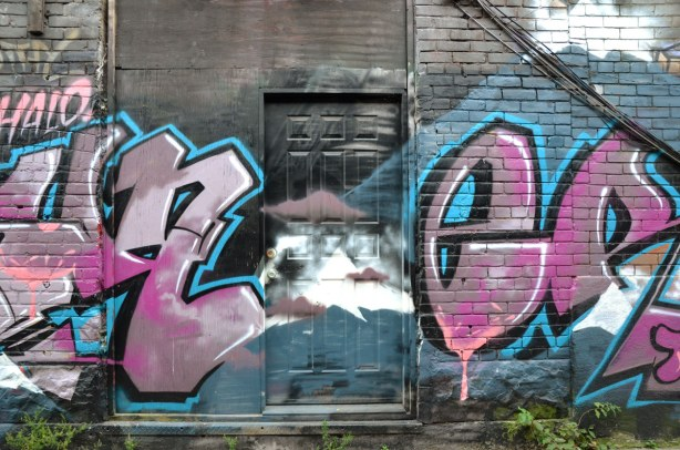 large pink graffiti tag letters on either side of a black door in an alley
