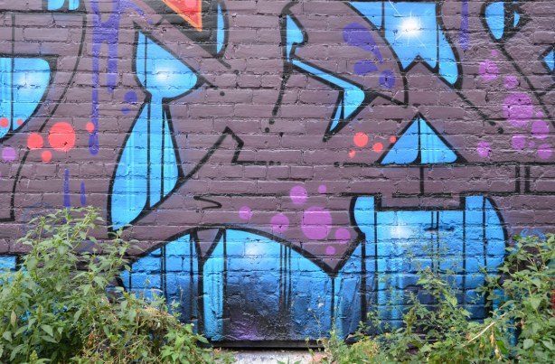 Part of a street art painting in blues and purples.  It looks very geometric in design.  Some weeds are growing up in front of it.
