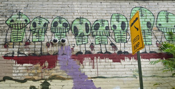 a line of graffiti little green guys that look sort of like aliens with stick arms and legs and big black eyes.