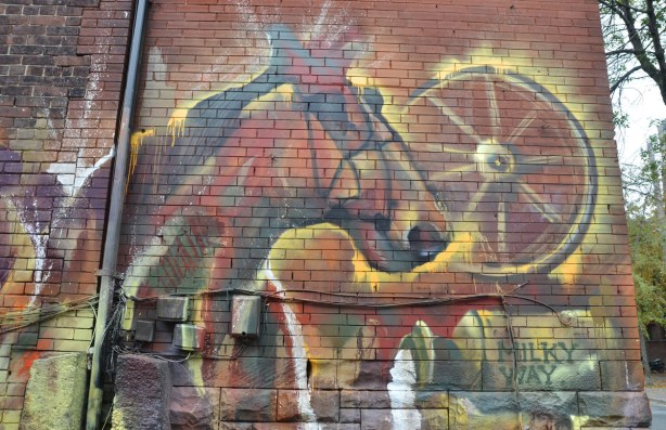 graffiti picture on a brick wall of a horse's head, a wagon wheel and spilt milk pouring from a large container.