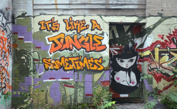 Large orange and yellow graffiti letters that say It's Like A Jungle Sometimes.  There is a door on the right side and on the door is a large black and white picture of a woman from the waist up.  She is bare chested with little pink hearts covering her nipples.