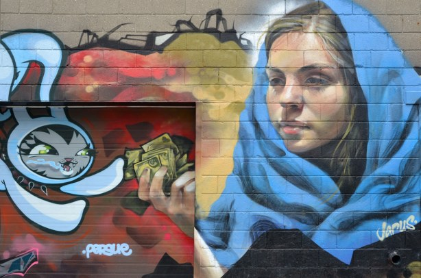 mural on a wall of a young woman with a large blue scarf handing money to a cartoon rabbit