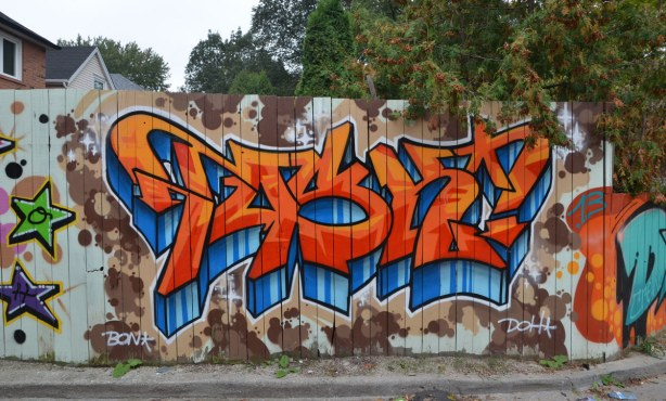 Large bright orange and blue tag on a wood fence