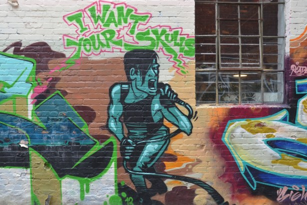 Graffiti on a wall with a window in the corner.  The picture is of a person singing into a microphone.  The words I want your skulls are above the person's head.