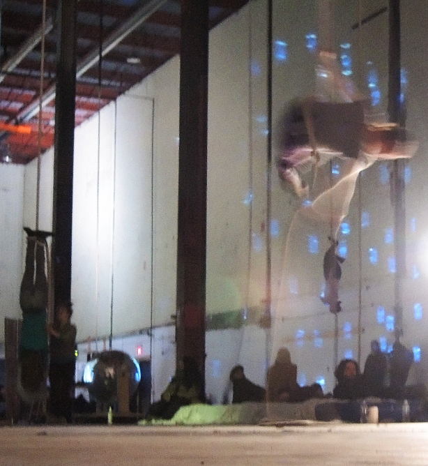 Three people are performing aerial movements on ropes hanging from the ceiling in a large dimly lit space