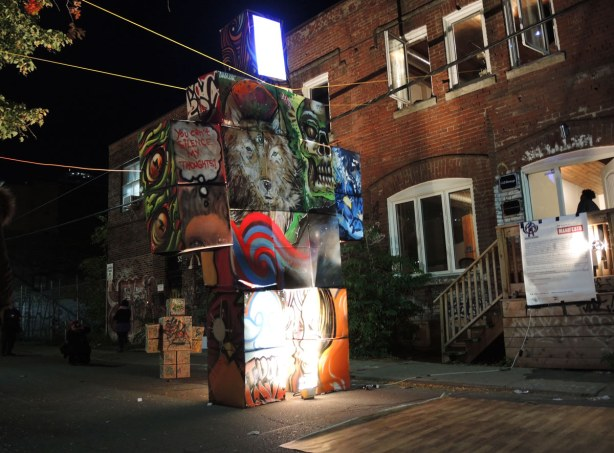 graffiti covered cardboard boxes put together in a robot shape.  The face (or head) is a white light.  It's an alley.