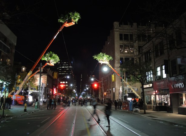 people on a street downtown at night.  3 large orange cranes with many small palm trees in their baskets overhand the street.  they are well lit from below.