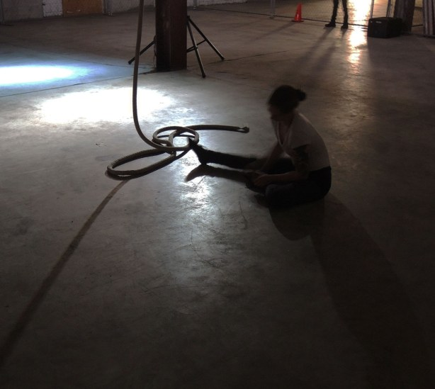 a woman is sitting on the ground with a large rope beside her.