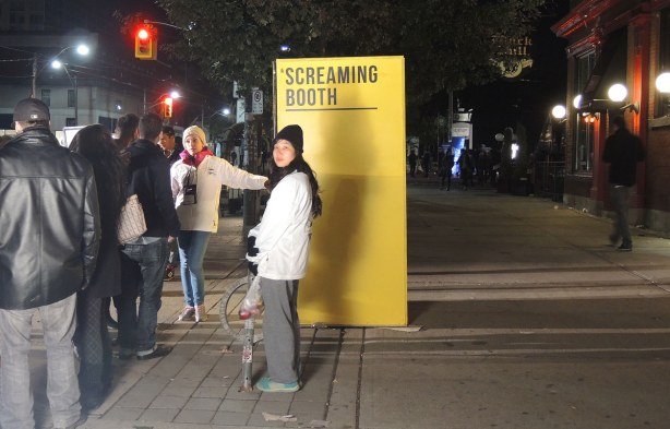 "A bright yellow box with the sign ""scraming booth"" sits on a sidewalk.  There is a line up of people waiting for their turn to scream."