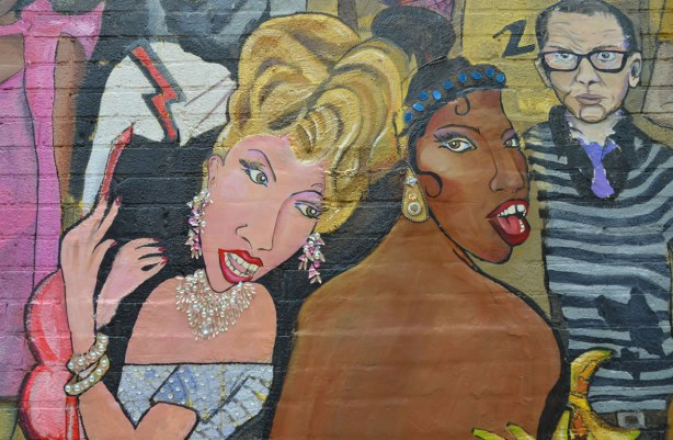 detail from mural - three people, black woman, white woman with blond hair and glittery ear rings and necklace, and a man in the right hand corner