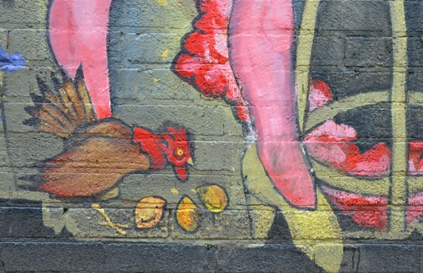detail from mural - chicken pecking at some nuts (corn?) on the ground beside legs wearing yellow high heel shoes
