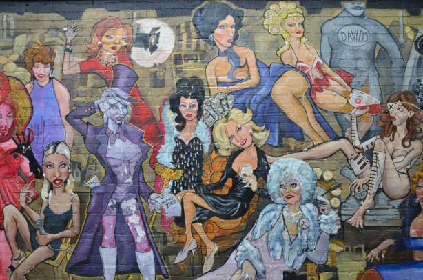 detail from mural - group of people in flamboyant clothes lounging around